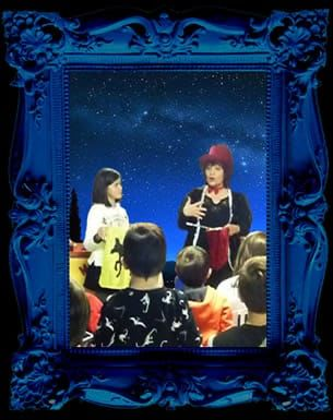 Magic valery speaks to an audience of children, in the background a starry night
